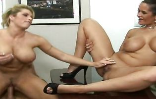 Two busty babes get roughly drilled in an office thresome